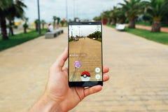 BATUMI, GEÓRGIA 14 DE JULHO DE 2016: A mão que guarda o smartphone para jogar o jogo da realidade aumentada Pokemon vai Fotos de Stock Royalty Free
