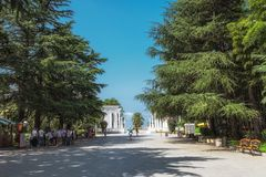 Batumi Georgië - September 2, 2014 Strandboulevard met bomen, mensen en witte kolombouw royalty-vrije stock afbeelding
