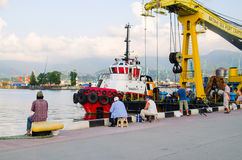 BATUMI, GEORGIA - 8 agosto 2016: Il porto marittimo è il posto favorito dei pescatori locali, venente qui ogni giorno con l'amico Immagini Stock