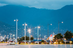 Batumi Georgia Crossing Rows Of Luminous Lampposts At Quay. Mountain View In Evening Haze Background. Stock Image