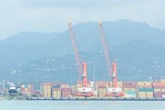 BATUMI, GEORGIA - 8 LUGLIO 2017: Grandi gru e contenitori del porto Montagne nei precedenti Fotografie Stock