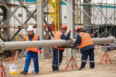 Bau der Anlage auf der Verarbeitung von Kohlenwasserstoffe Arbeitskräften die Rohrleitung anbringen stockbilder