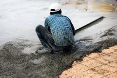 Bau, der für konkreten Boden arbeitet Stockbild