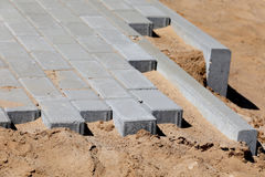 Bau der Pflasterung mit konkretem Ziegelstein Lizenzfreie Stockfotos