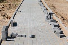 Bau der Pflasterung mit konkretem Ziegelstein Stockfotografie