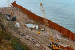Bau der Promenade in Meer, die Seeküstenlinie verstärkend, spezielle Ausrüstung auf dem Strand Lizenzfreie Stockbilder