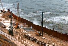Bau der Promenade in Meer, die Seeküstenlinie verstärkend, spezielle Ausrüstung auf dem Strand Lizenzfreie Stockfotos