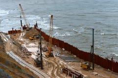 Bau der Promenade in Meer, die Seeküstenlinie verstärkend, spezielle Ausrüstung auf dem Strand Stockbild
