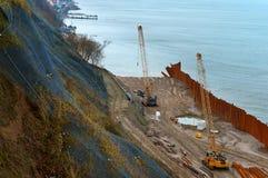 Bau der Promenade in Meer, die Seeküstenlinie verstärkend, spezielle Ausrüstung auf dem Strand Stockfoto