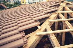 Bau des neuen Hauses, Dachgebäude mit braunen Fliesen und Bauholz Auftragnehmergebäudedach des neuen Hauses Lizenzfreie Stockfotos