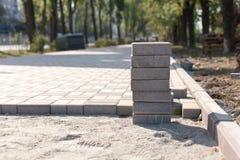 Bau einer neuen Pflasterung des Pflastersteinnahaufnahmedetails Pflasterungskopfstein blockiert Bau des Weges, der Straße oder de Stockbild