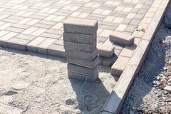 Bau einer neuen Pflasterung des Pflastersteinnahaufnahmedetails Pflasterungskopfstein blockiert Bau des Weges, der Straße oder de Stockfotos