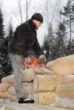 Bau eines Klotzblockhauses, ein junger Arbeitnehmer sägt Klotz, usin Stockfotos