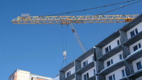 Bau eines mehrstöckigen Gebäudes Baukran hebt die Betonplatte über dem Dach an stock video