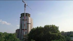 Bau eines mehrstöckigen hohen Hauses, ein Turmkran an einer Baustelle, eine Ansicht des Baus von einem modernen stock footage