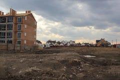 Bau eines neuen unfertigen Wohnhauses gegen Privathäuser im Hintergrund lizenzfreie stockbilder