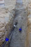 Bau eines neuen Wasserversorgungssystems, Rohr im Graben Stockfotografie
