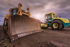 Bau eines Schotterwegs in Spanien unter Verwendung eines Baggers und eines Bodenverdichters stockbilder