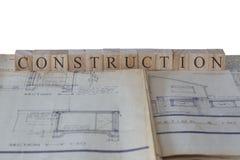 Bau geschrieben auf Holzklötze auf Hauserweiterungs-Bauplanplänen stockfoto
