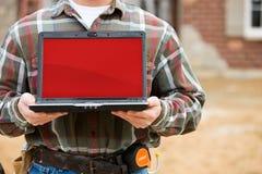 Bau: Halten des Laptops mit leerem Bildschirm Stockfotografie