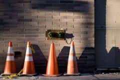Bau-Kegel, die warten, auf dem Bürgersteig verwendet zu werden Lizenzfreie Stockfotos