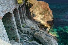 Bau mit felsiger Küste des Bogens u. lichtdurchlässigem Meer stockfoto