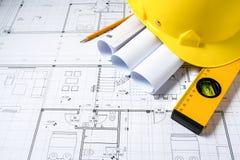 Bau plant mit Sturzhelm und Ziehwerkzeugen auf Plänen stockfotos