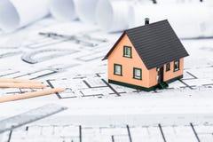 Bau plant mit Ziehwerkzeugen und Haus-Miniatur auf Blauem Stockfotos
