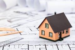 Bau plant mit Ziehwerkzeugen und Haus-Miniatur auf Blauem Lizenzfreies Stockbild