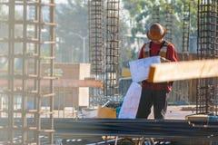 Bau-Vorarbeiter schaut über Plänen am Ort stockbild
