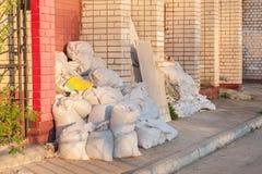 Bauabfall in den weißen Bautaschen liegen auf der Straße nahe der Backsteinmauer Stockfotos