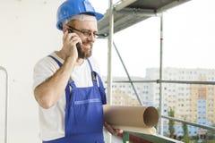 Bauarbeiter in Arbeitsausstattung und im Sturzhelm, der an der großen Höhe auf einer Baustelle mit Plänen unter seinem steht Lizenzfreies Stockfoto
