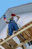Bauarbeiter auf Gestell mit Bohrgerätperforator Stockbild
