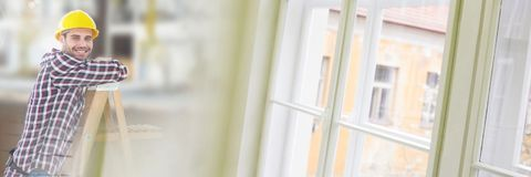 Bauarbeiter auf Leiter vor Baustelle mit Fensterübergangseffekt Stockfotos