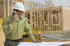 Bauarbeiter-With Blueprints And-Mobiltelefon lizenzfreie stockfotografie