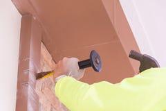 Bauarbeiter, der alten Ziegelstein demoliert Lizenzfreie Stockfotos