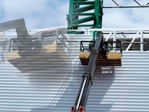 Bauarbeiter an der Baustelle unter Verwendung der anhebenden Boommaschinerie lizenzfreie stockbilder