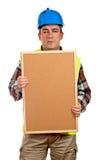Bauarbeiter, der das leere corkboard anhält Stockfotografie