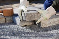 Bauarbeiter, der die Ziegelsteinstraße pflastert Stockbilder