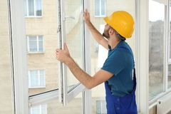 Bauarbeiter, der Fenster in Haus installiert stockbild