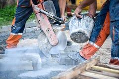 Bauarbeiter, der konkrete Pflasterungsstöße oder Metall für s schneidet Lizenzfreie Stockfotografie