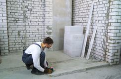 Bauarbeiter, der Maße mit Laser-Niveau an der Baustelle tut stockfotos