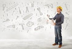 Bauarbeiter, der mit Hand gezeichneten Werkzeugikonen planiert stockfotografie