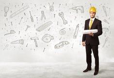 Bauarbeiter, der mit Hand gezeichneten Werkzeugikonen planiert Stockbilder