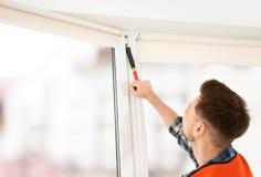 Bauarbeiter, der Plastikfenster installiert lizenzfreie stockbilder