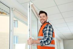 Bauarbeiter, der Plastikfenster installiert lizenzfreies stockfoto