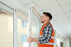 Bauarbeiter, der Plastikfenster installiert stockbilder