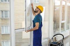Bauarbeiter, der Plastikfenster installiert lizenzfreie stockfotografie