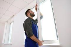 Bauarbeiter, der Plastikfenster installiert stockfoto