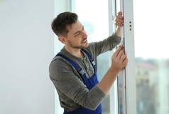 Bauarbeiter, der Plastikfenster installiert stockfotos